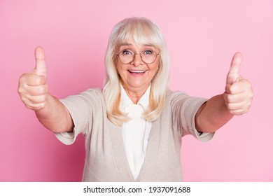 Photo portrait of elderly lady giving two thumbs up isolated on pastel pink colored background