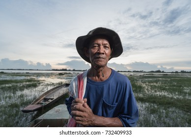Photo portrait of the elderly native Fisher,who are out fishing in the river with boats background.