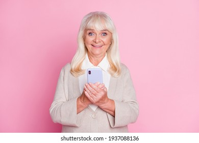 Photo portrait of elderly woman holding phone in two hands isolated on pastel pink colored background