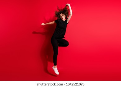 Photo portrait full body view of wild girl jumping up dancing isolated on vivid red colored background