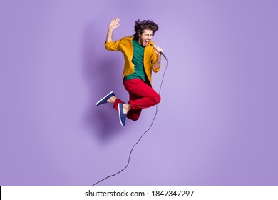 Photo portrait full body view of guy shouting singing into mic jumping up isolated on vivid purple colored background