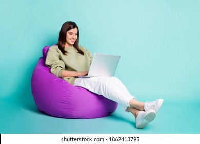Photo portrait full body view of woman typing on laptop sitting in purple armchair isolated on vivid turquoise colored background - Shutterstock ID 1862413795