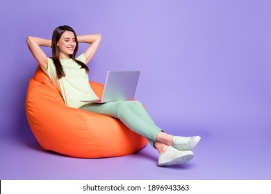 Photo portrait full body view of girl relaxing with laptop hands behind head in bean bag chair isolated on vivid violet colored background