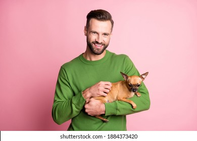 Photo portrait of happy cheerful man keeping small best friend brown dog isolated pastel pink color background
