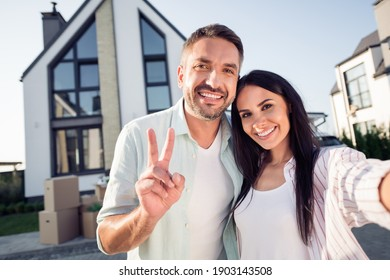 Photo portrait of happy family couple wife husband showing v-sign smiling outside new home after moving relocating