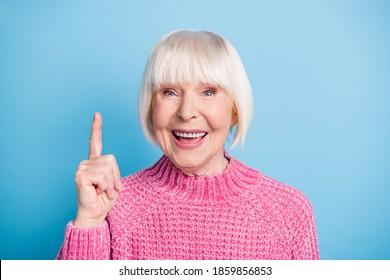 Photo portrait of happy old lady having idea raising finger up isolated on pastel blue colored background