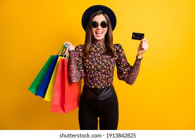 Photo portrait of happy smiling girl in hat showing card in keeping packages after sale isolated on bright yellow color background