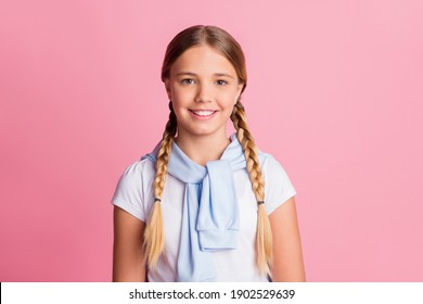 Photo portrait little schoolgirl wearing braids white t-shirt smiling isolated on pastel pink color background