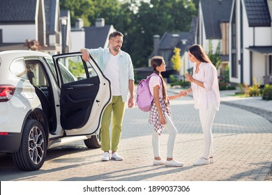 Photo portrait of mother giving daughter advice for first school day while father waits outside white car on street in summer