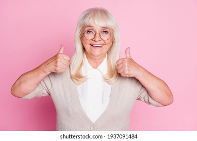 Photo portrait of old lady showing two thumbs up isolated on pastel pink colored background