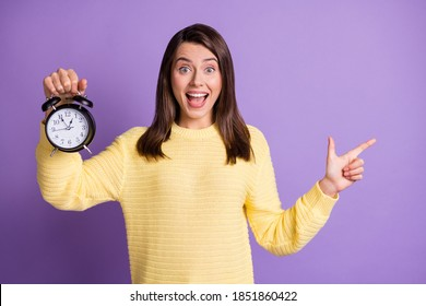 Photo portrait of positive woman holding clock with one hand pointing finger to side with open mouth isolated on vivid purple colored background