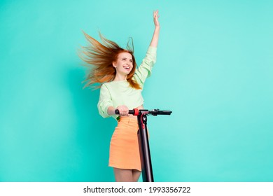 Photo portrait of red haired girl smiling riding urban electro scooter waving hand isolated vibrant teal color background