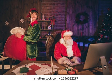 Photo portrait of santa claus working on pc and elf carrying big red present sack looking behind back