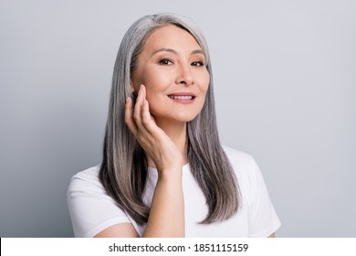 Photo portrait of senior woman with grey hair touching cheek wearing white t-shirt smiling isolated on grey color background