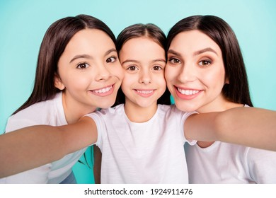 Photo portrait of three cheerful sisters smiling taking selfie isolated on bright blue color background