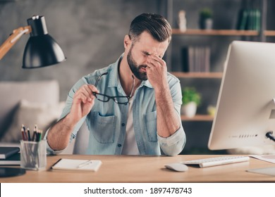 Photo portrait of tired guy having headache holding nose bridge with fingers at table in modern industrial office indoors