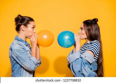 Photo portrait of two brunette hair lady look to each other blow fly ball stand isolated on yellow shine background make staring eyes big cheeks