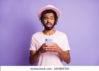 Photo portrait of upset guy holding phone in two hands isolated on vivid violet colored background