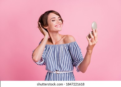Photo portrait of young pretty girl looking at mirror touching bob hairstyle smiling cheerfully isolated on pastel pink color background