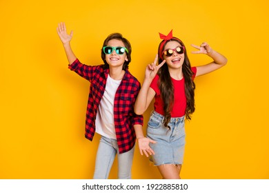 Photo of positive boy hands palms girl fingers show v-sign have good mood isolated on yellow color background
