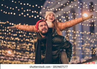 Photo of positive couple having fun christmas x-mas around evening outside illumination boyfriend piggyback girlfriend holding hands fly - Shutterstock ID 1819607177