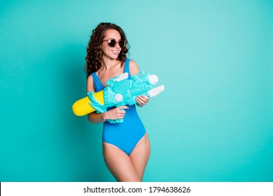 Photo of positive girl funky player shoot water gun empty space her friend pool party battle opponent wear blue swimsuit isolated over turquoise color background