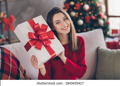 Photo of positive girl sit divan hold big gift box wear red pullover in house indoors with x-mas newyear advent ornament