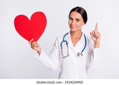 Photo of positive pretty lady doctor dressed uniform smiling holding red heart pointing empty space isolated white color background