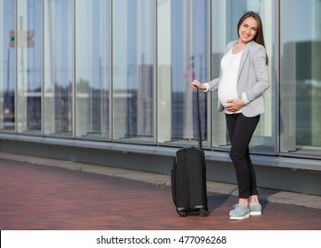 Photo of pregnant business woman with suitcase in the city