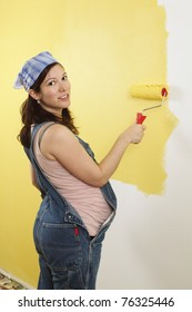 Photo of a pregnant female painting the wall of a bedroom for her future baby.
