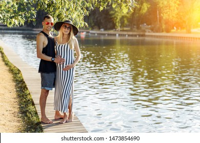 Photo of pregnant woman in hat and man standing on riverbank