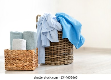 Photo of preparation to laundry process. Two wooden basket with fresh and clean towels, and dirty clothes standing on room floor inside bright apartment interior