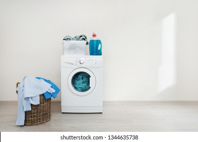 Photo of preparation to laundry process. White washing machine standing on laminate floor near wooden basket with clothes. Object isolated against wall inside bright light flat interior
