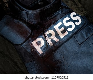 Photo of a press journalist armor war protective vest in blood splatter depicting mass media war victims.