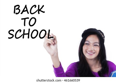 Photo of a pretty Asian schoolgirl writes Back to School on the whiteboard, isolated on white background