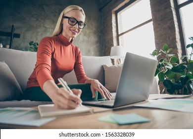 Photo of pretty business lady texting notebook colleagues working home noticing startup details in organizer wear specs casual clothes sitting comfy sofa indoors