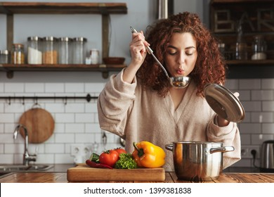 Photo of pretty caucasian woman holding cooking ladle spoon while eating soup with fresh vegetables in kitchen at home