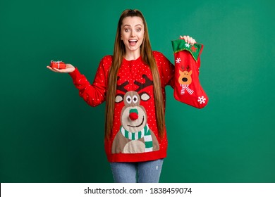 Photo of pretty charming lady hold newyear stocking x-mas present little giftbox jewelry from boyfriend open mouth overjoyed wear red ugly ornament pullover isolated green color background