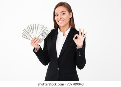 Photo of pretty cheerful business woman standing isolated over white background showing okay gesture holding money. Looking camera.