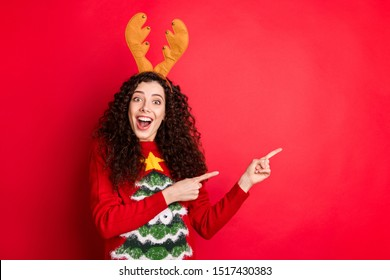 Photo of pretty curly lady indicating fingers empty space presenting x-mas sale shopping wear head horns knitted funny pullover isolated red color background