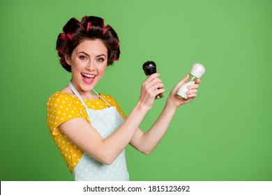 Photo of pretty cute girlish young lady roller hairstyle hold pepper shaker salt bottle open mouth pretend mexican dancer wear dotted apron shirt isolated green color background
