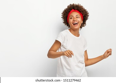 Photo of pretty dark skinned woman stands sideways, feels energized dances actively to music wears red headband casual white t shirt poses indoor. Horizontal shot of lovely African American girl moves
