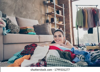 Photo of pretty dreamy lady stay home quarantine lying many clothes heap stack floor wardrobe stuff spring cleaning carefree mood want buy more shopping addiction living room indoors
