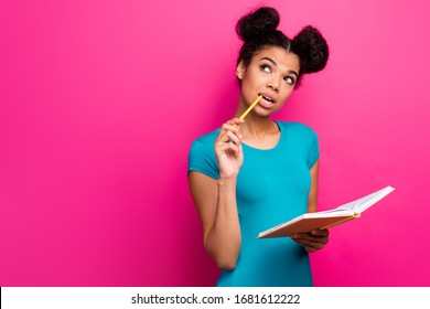 Photo of pretty funny dark skin lady two buns hold pencil in mouth look up empty space writing notes planner wear blue casual t-shirt isolated vibrant pink color background