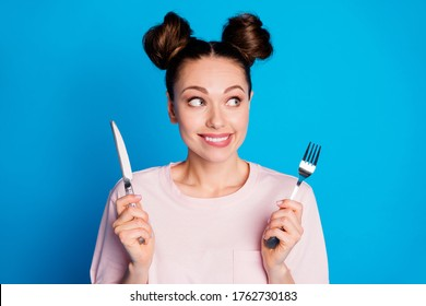 Photo of pretty funny hungry lady two funny buns hold fork knife wait tasty meal excited dinner start look side empty space wear casual pink t-shirt isolated bright blue color background