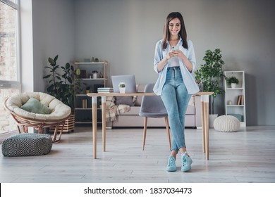 Photo of pretty girl hold telephone look screen crossed legs wear glasses jeans footwear shirt in home office indoors
