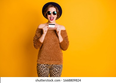 Photo of pretty lady open mouth hold plastic credit card excited good mood shopaholic make online payment wear soft sweater retro cap sun specs pants isolated yellow color background