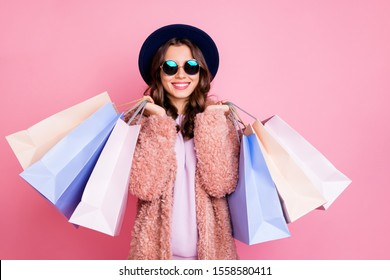 Photo of pretty millennial model lady carry many packs shopper enjoy tourism abroad sales wear fluffy jacket sun specs vintage blue hat isolated pink background
