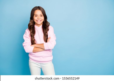 Photo of pretty small lady long wavy hairstyle holding hands crossed toothy smiling wear casual hoodie pullover pink isolated blue color background