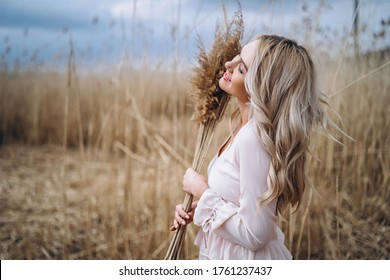Photo of a pretty smiling girl with long blond curly hair in light long drees sitting in a reed field and holding high reed branches in her hands